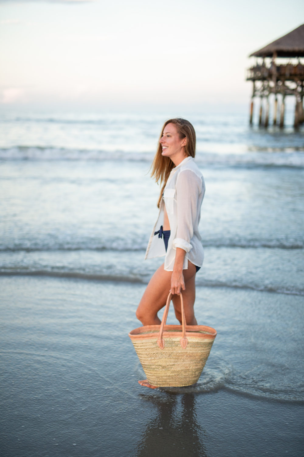 What to Pack in a Beach Bag: 20 Beach Essentials, Wearing Navy High Waisted Swimsuit, White Linen Shirt and Woven Straw Beach Bag | Sunshine Style