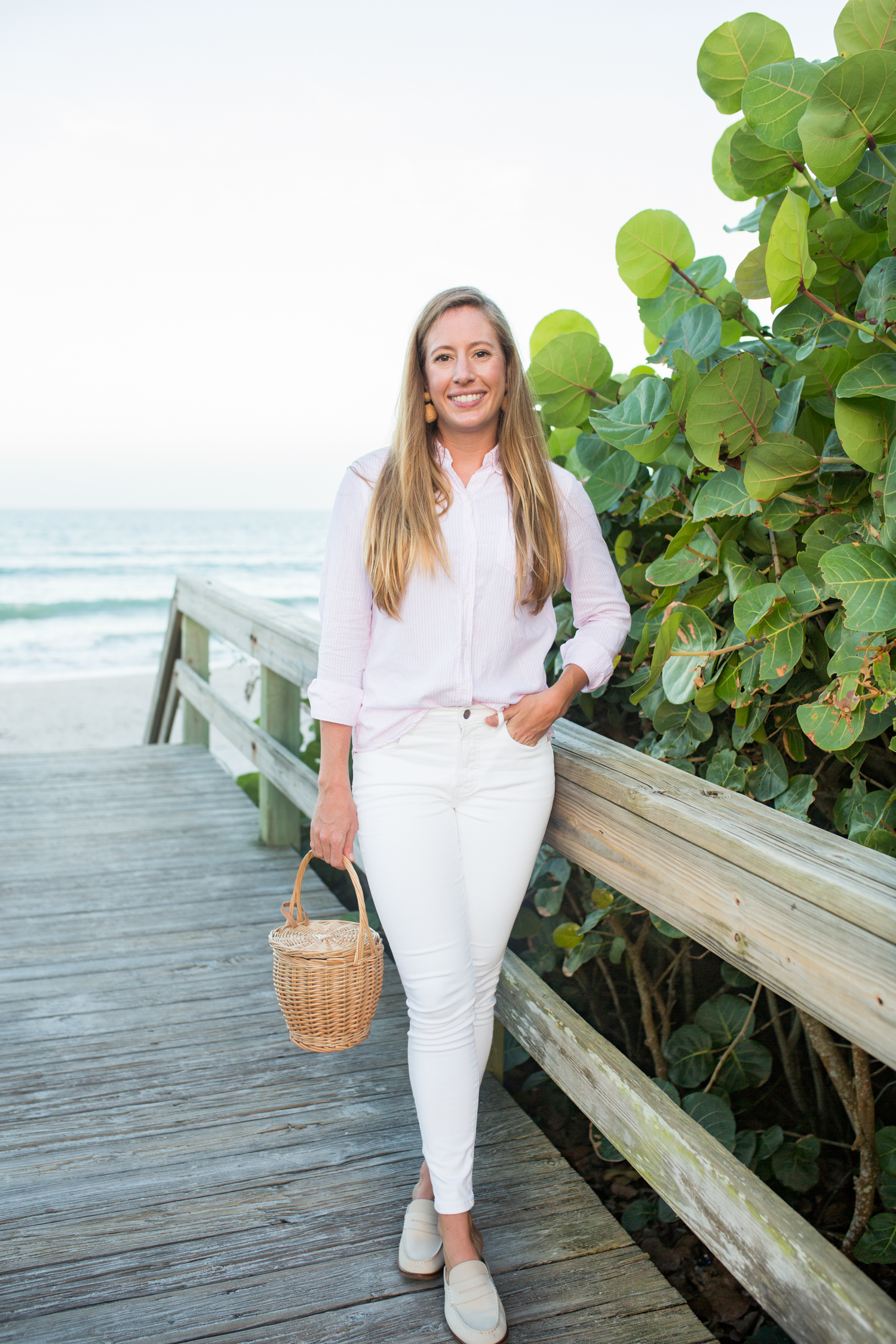 Woman at the beach wearing pink button down top and white jeans as timeless wardrobe essentials.