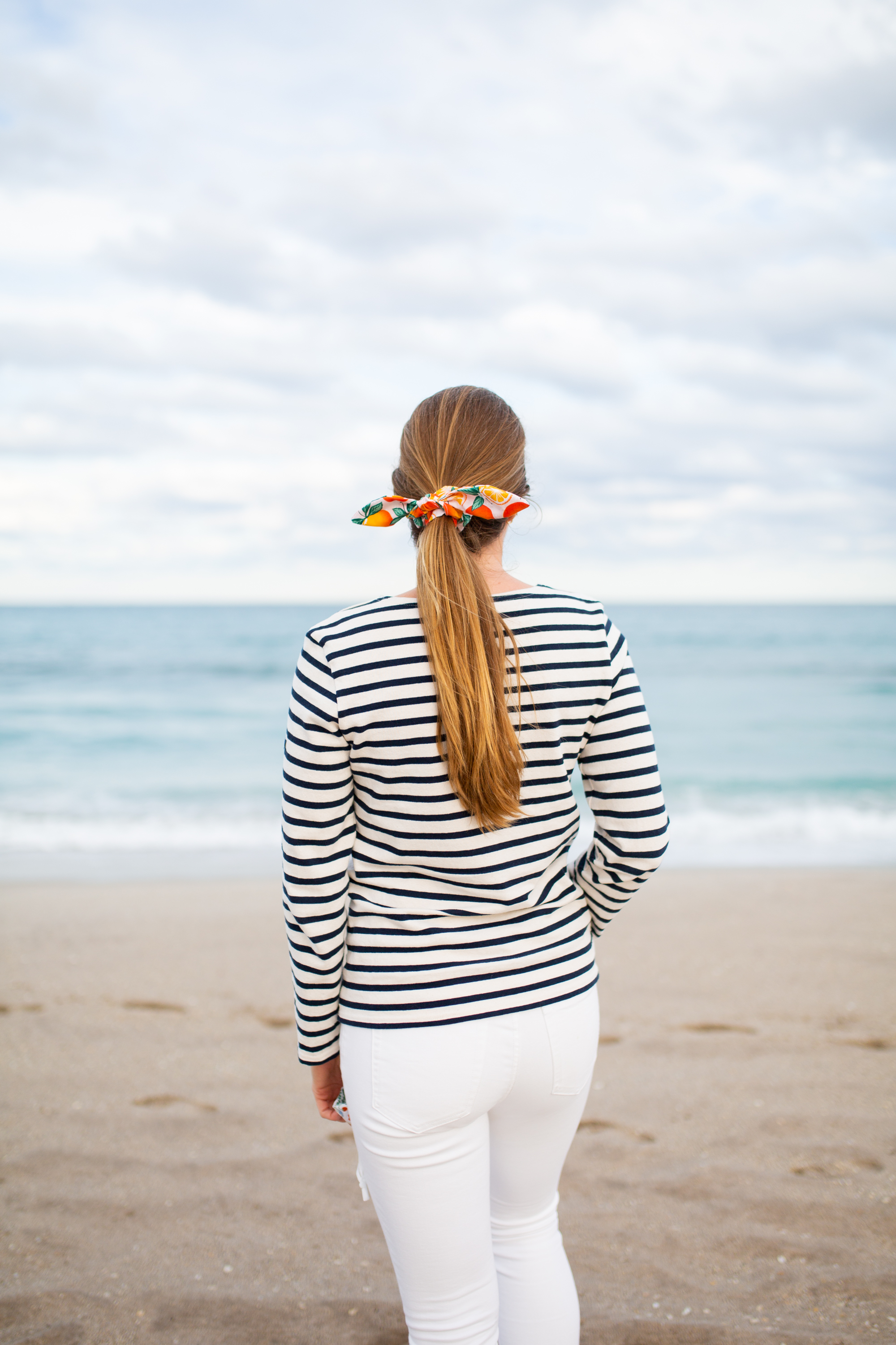 woman standing at the shore wearing striped shirt, white pants, and hair is tied for working full time, running a business, and blogging post