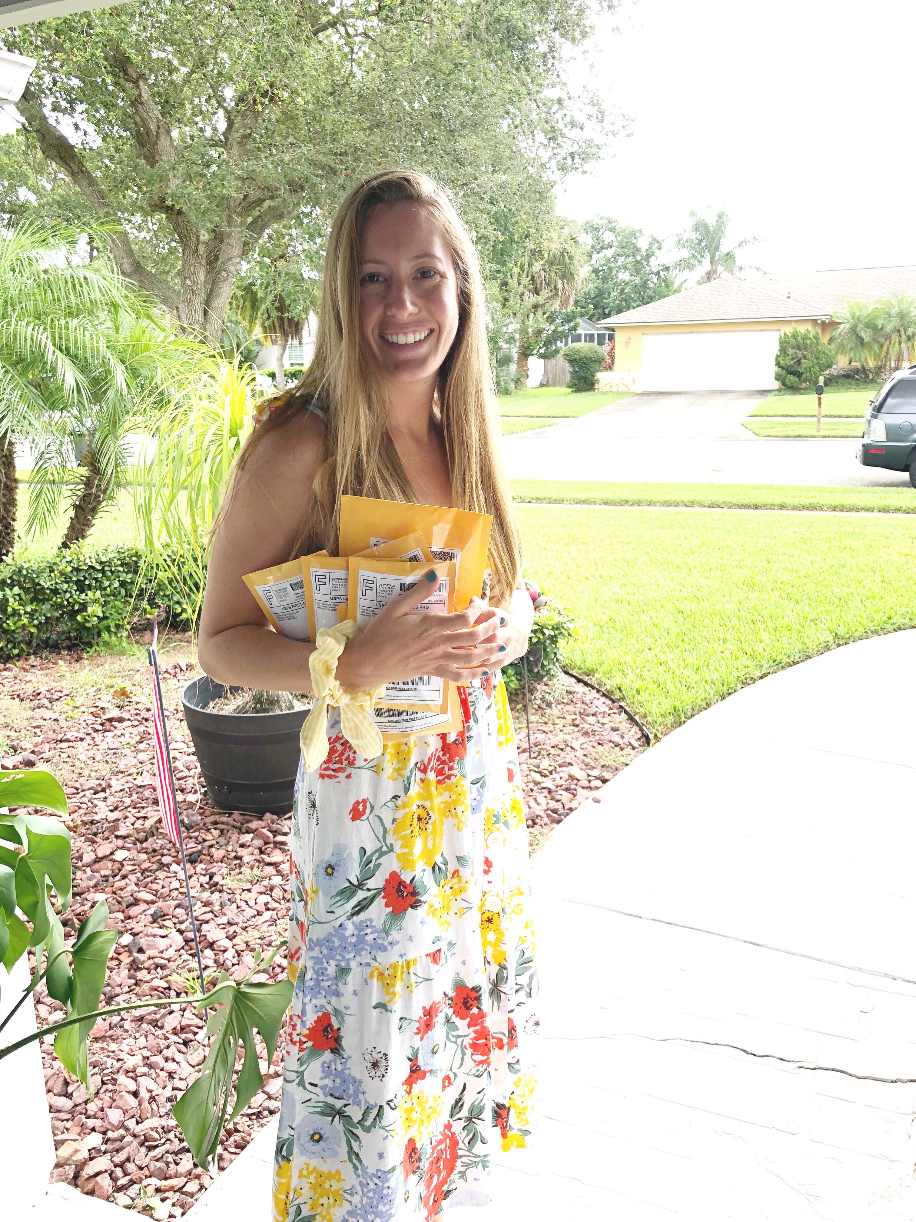 woman wearing a floral dress and holding packages for working full time and running a small business