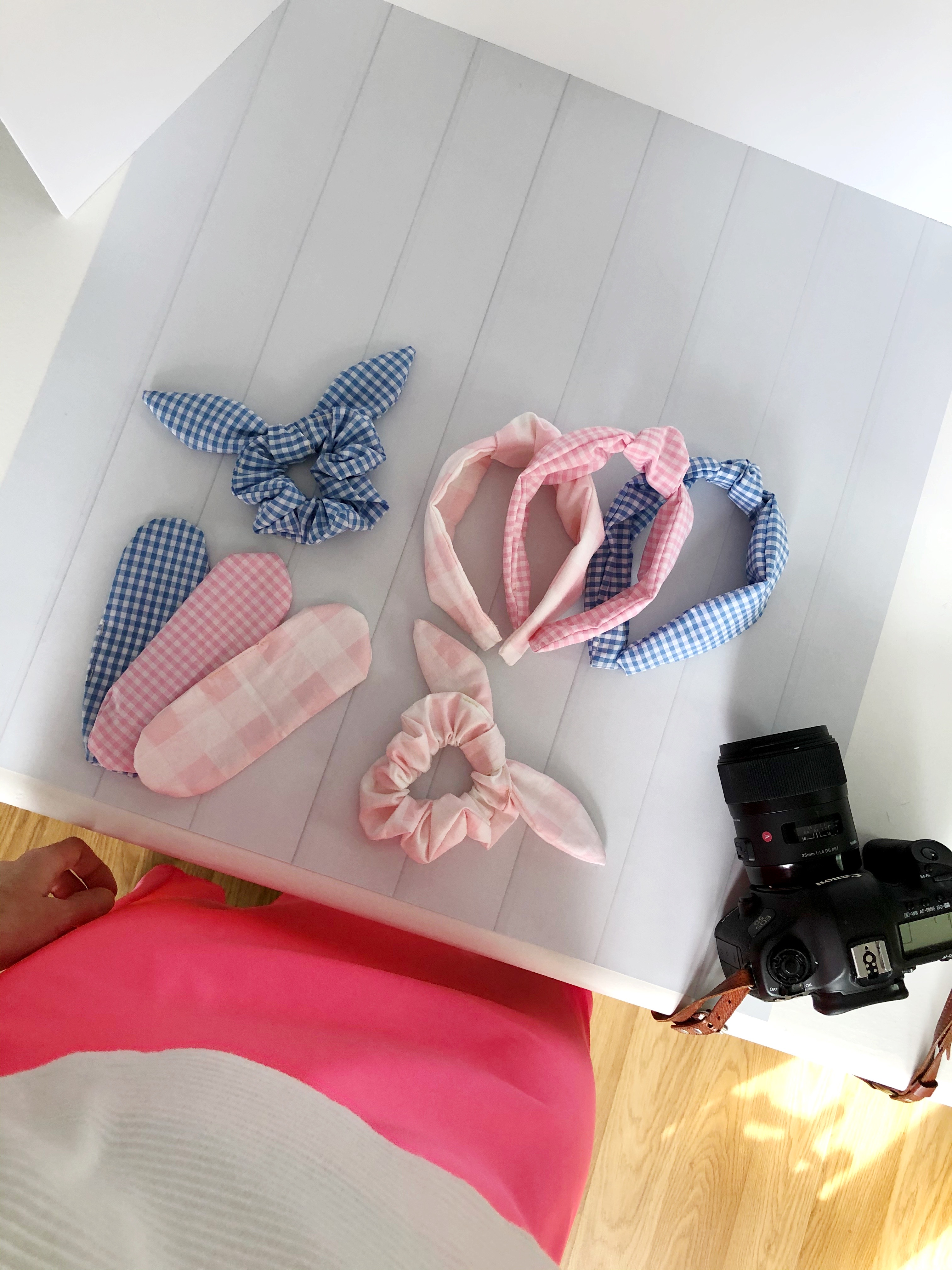 hair ties, headband, and a camera on a white table