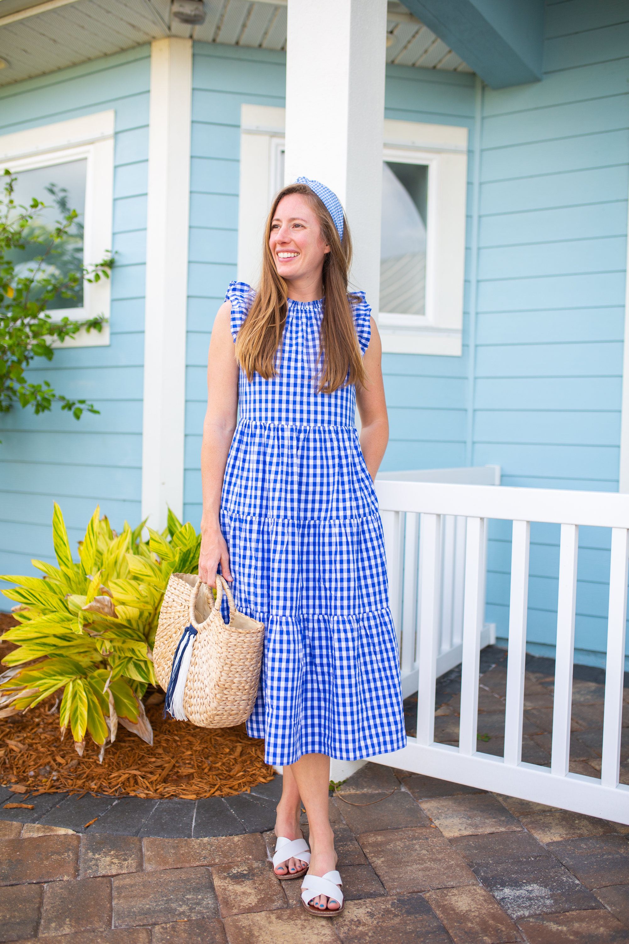 woman wearing a white sandals, holding a bag, and wearing J.Crew Gingham Tiered Dress