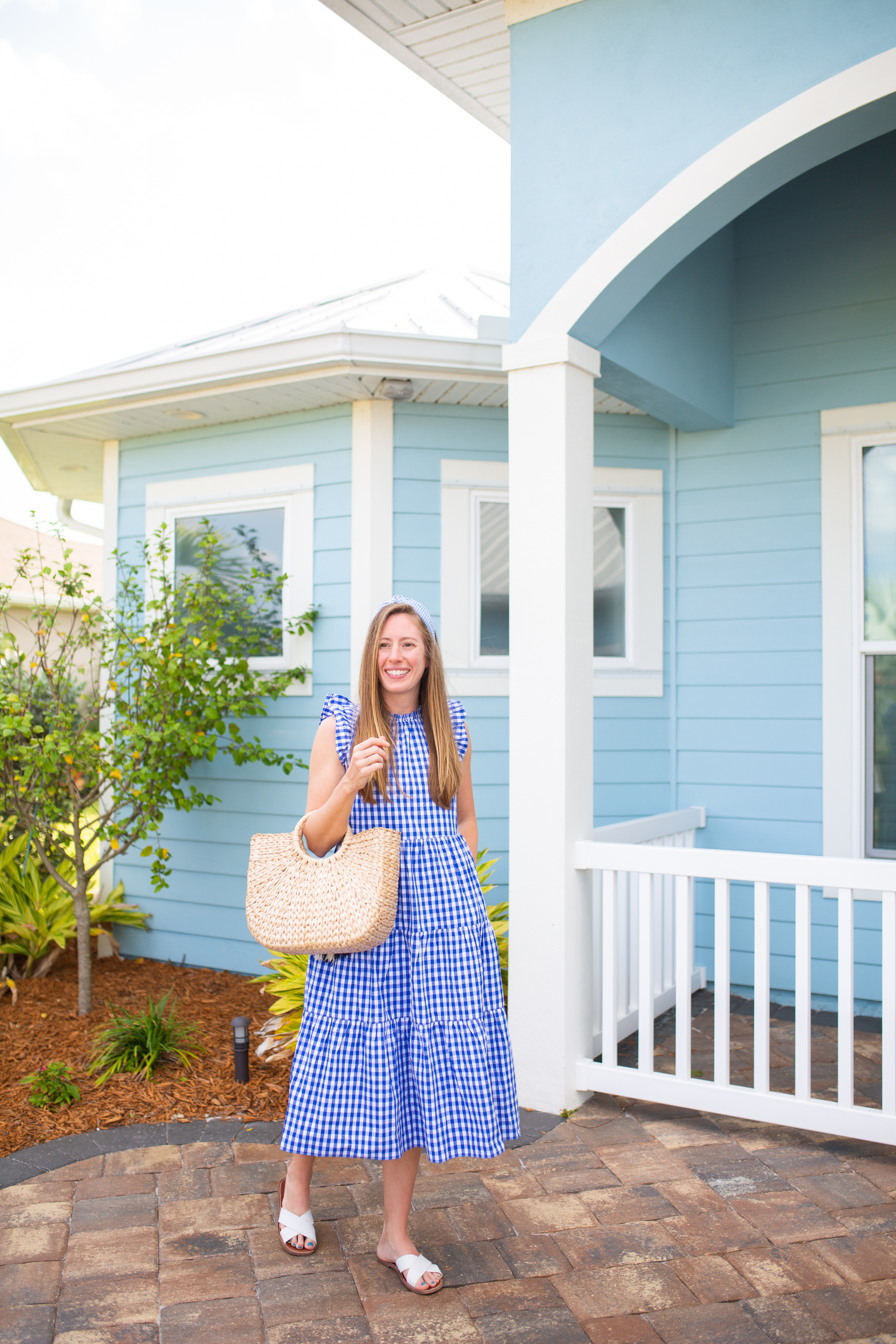 woman wearing J.Crew Gingham Tiered Dress in blue, holding a bag, and standing outside a blue house