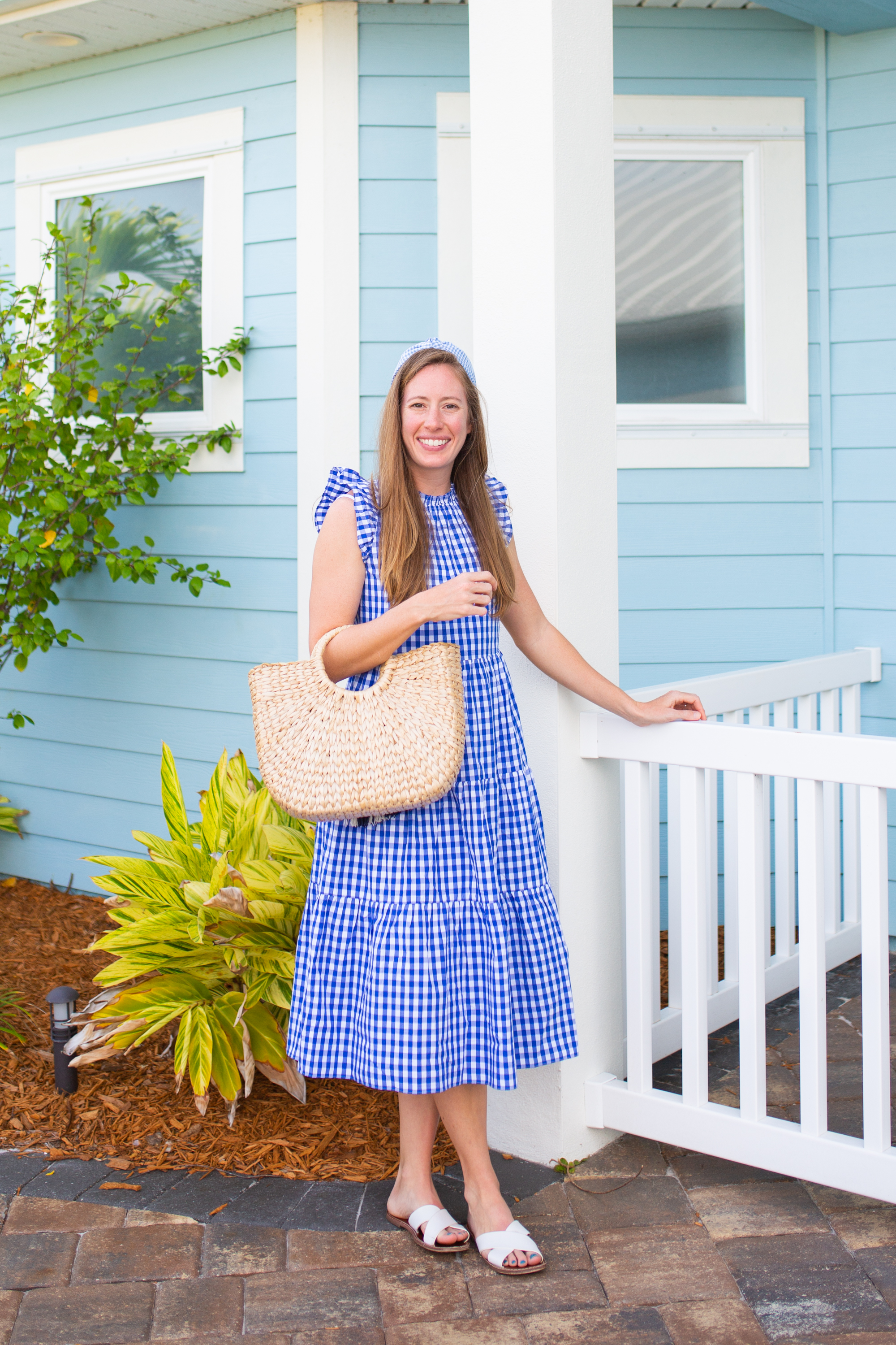 woman standing outside a blue house and wearing a blue dress