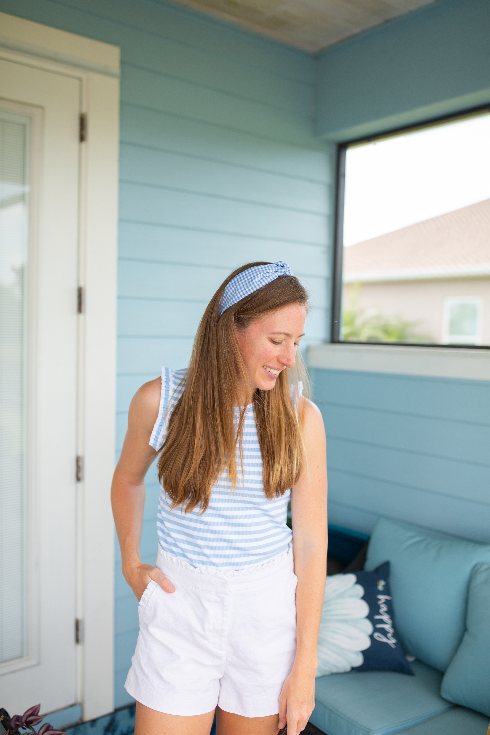 woman wearing Casual Summer Outfit of white shorts, shirt, and headband