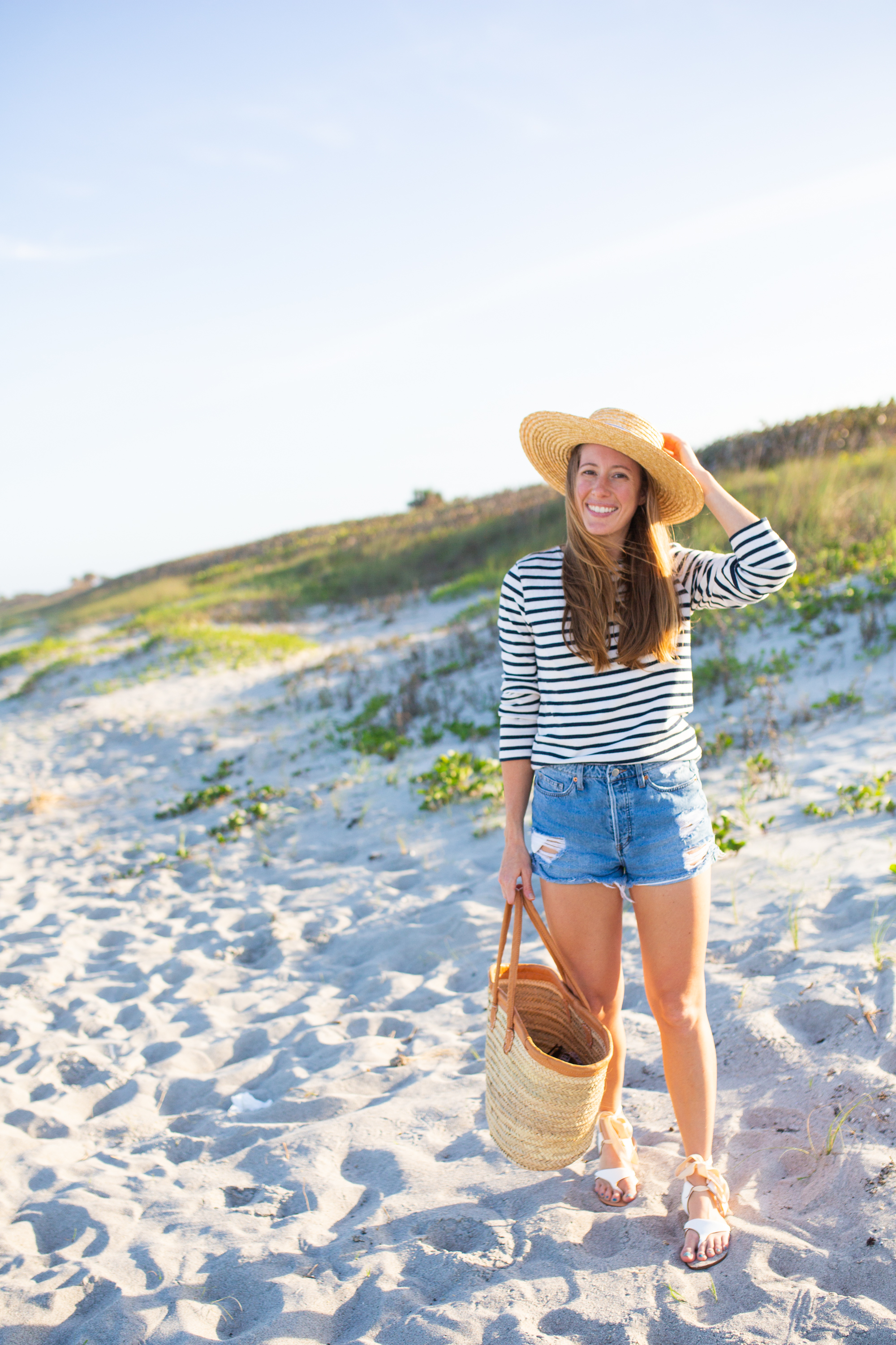 woman at the beach and holding her beach hat and bag to share Sarah Flint Grear Sandals Review