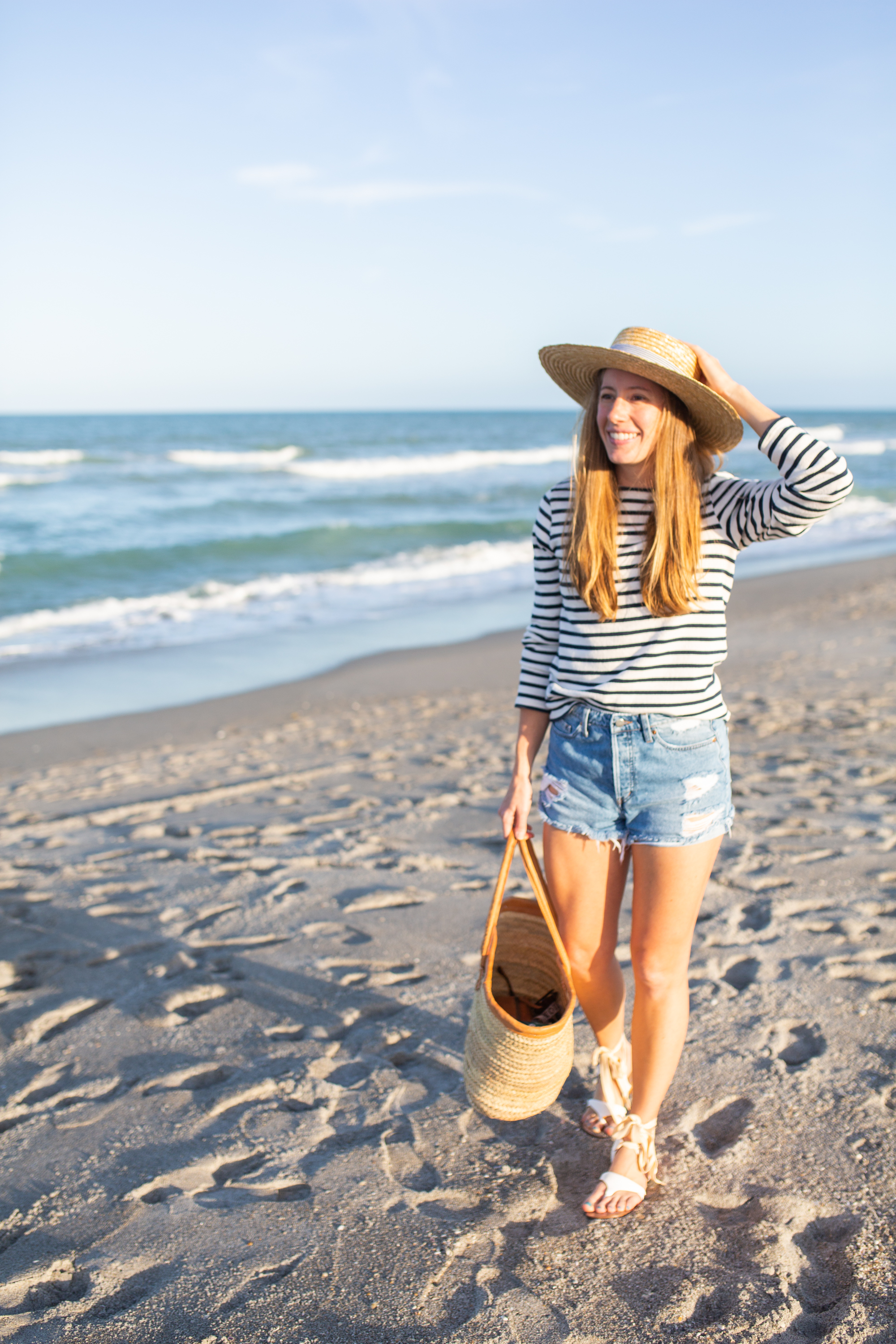 woman wearing denim shorts, long sleeves top, and beach hat and standing at the shore