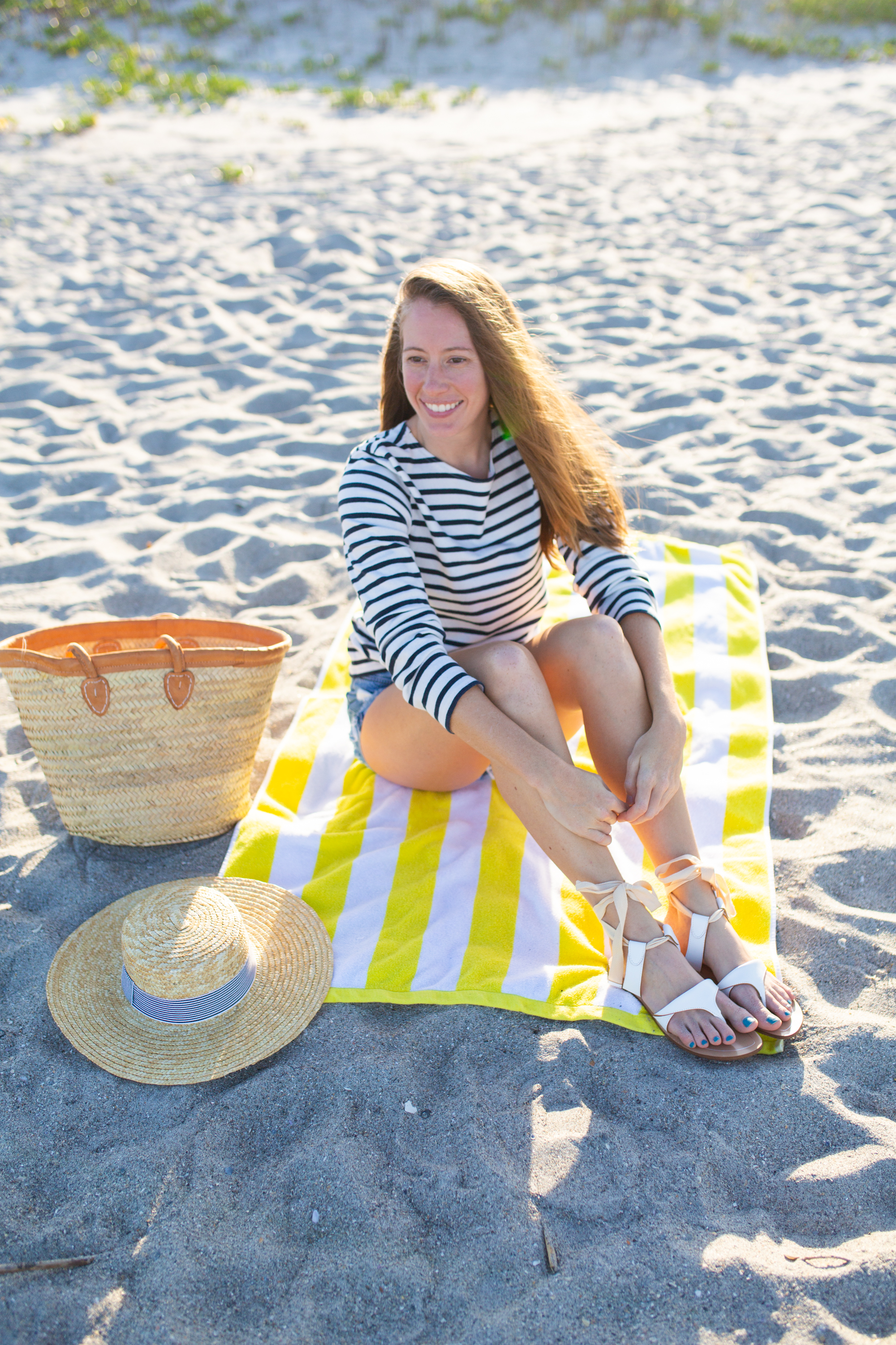 woman sitting at the beach and sitting at a beach towel with bag and hat