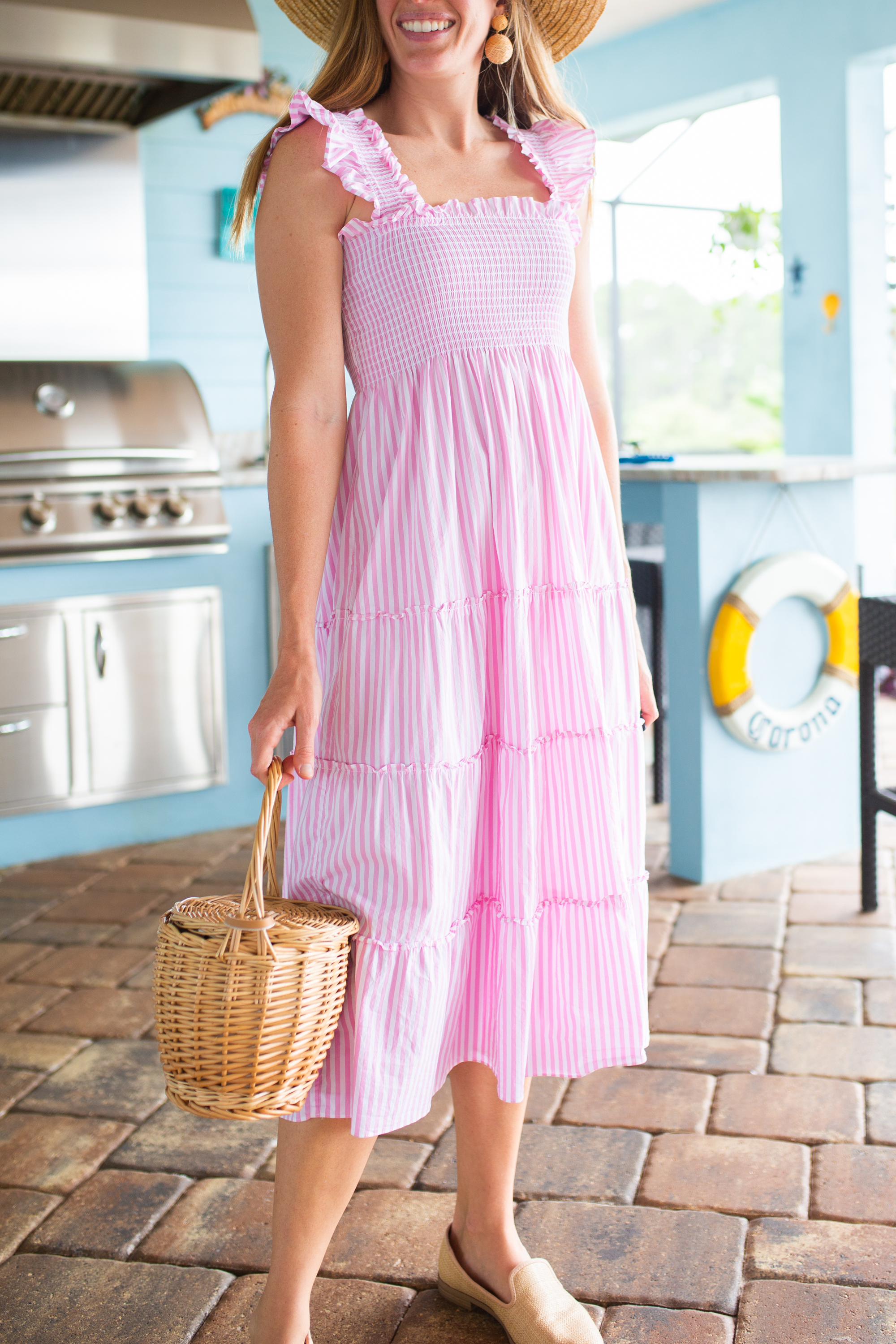 woman wearing pink dress for Nap Dress Review and holding a weaved bag