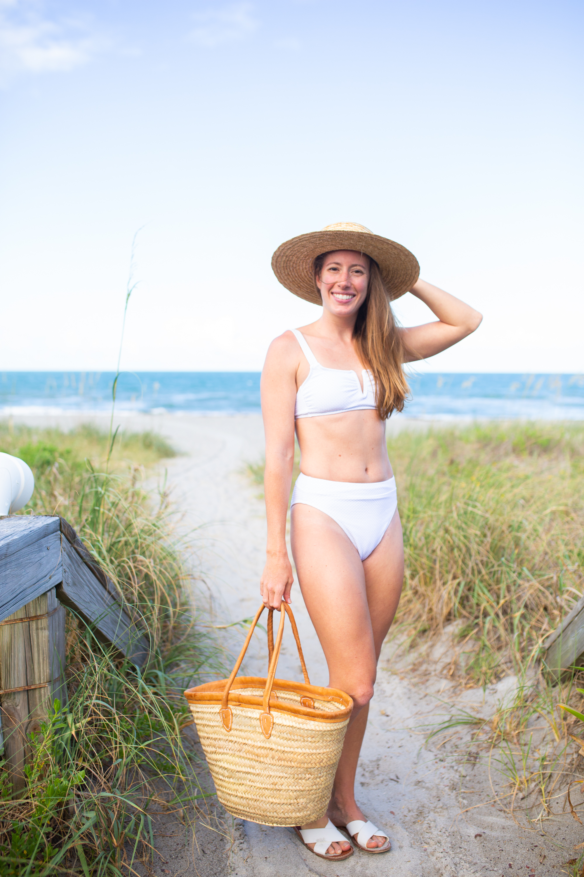 woman at the beach and wearing Classic White Swimsuits, weaved hat, and white flat sandals