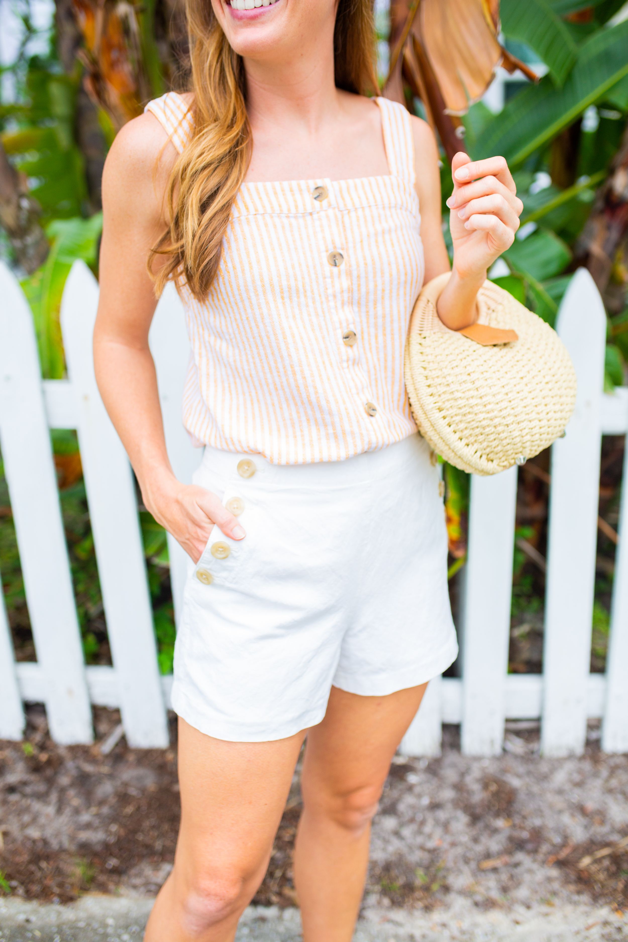 woman wearing striped top, white shorts, and weaved bag