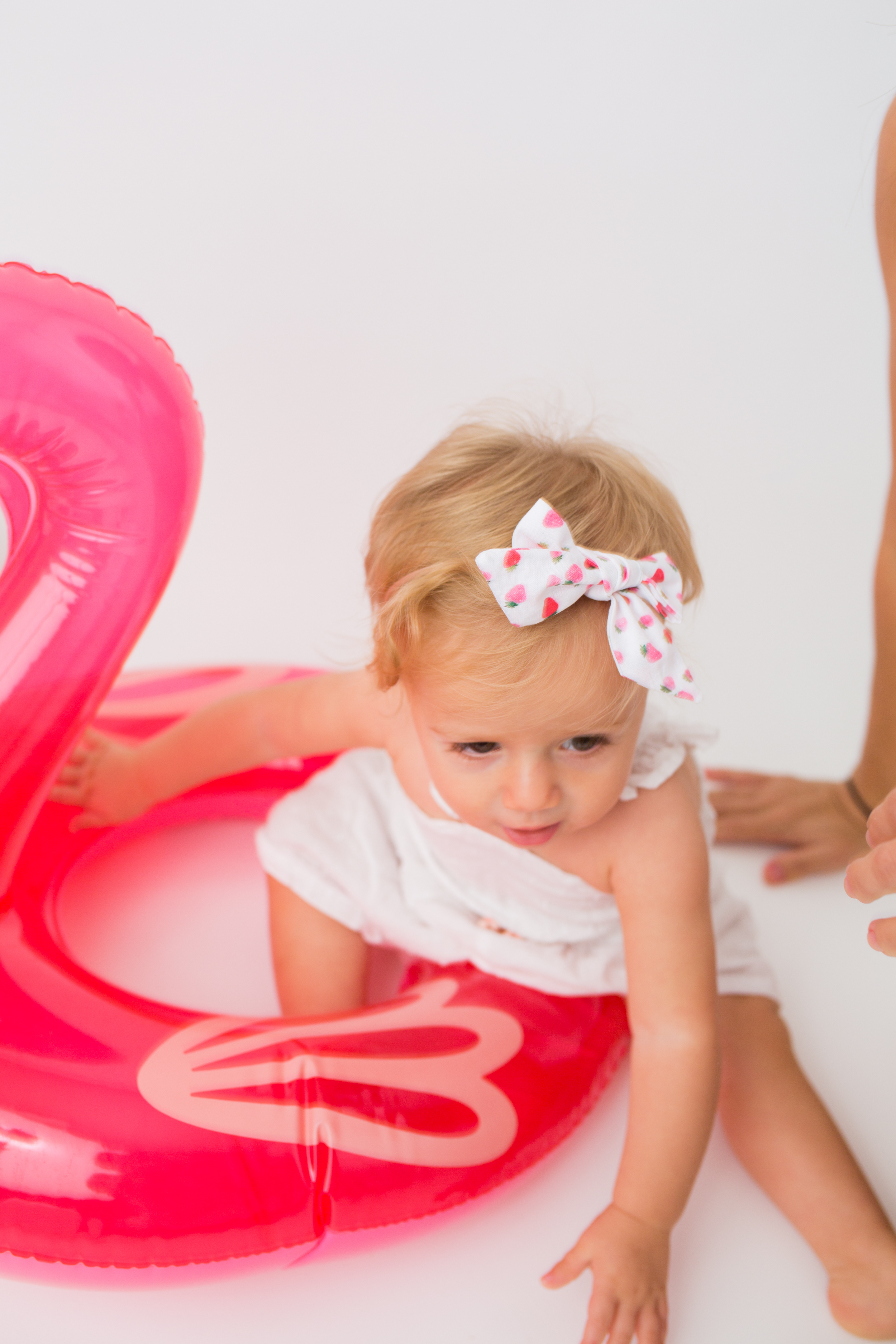 child wearing ribbon and playing with flamingo balloon from Sunshine Style Headbands