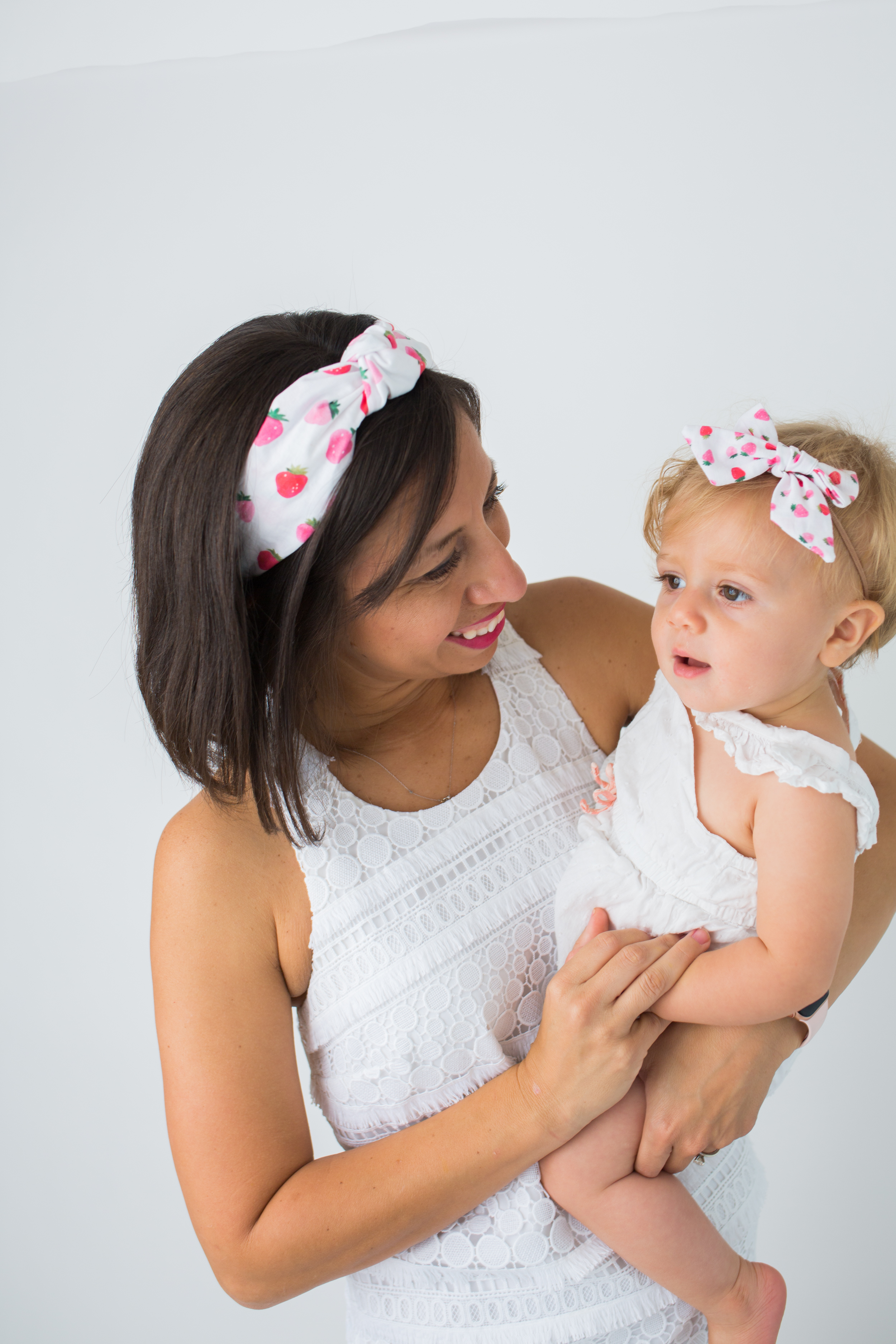 woman carrying her child and wearing Sunshine Style Headbands