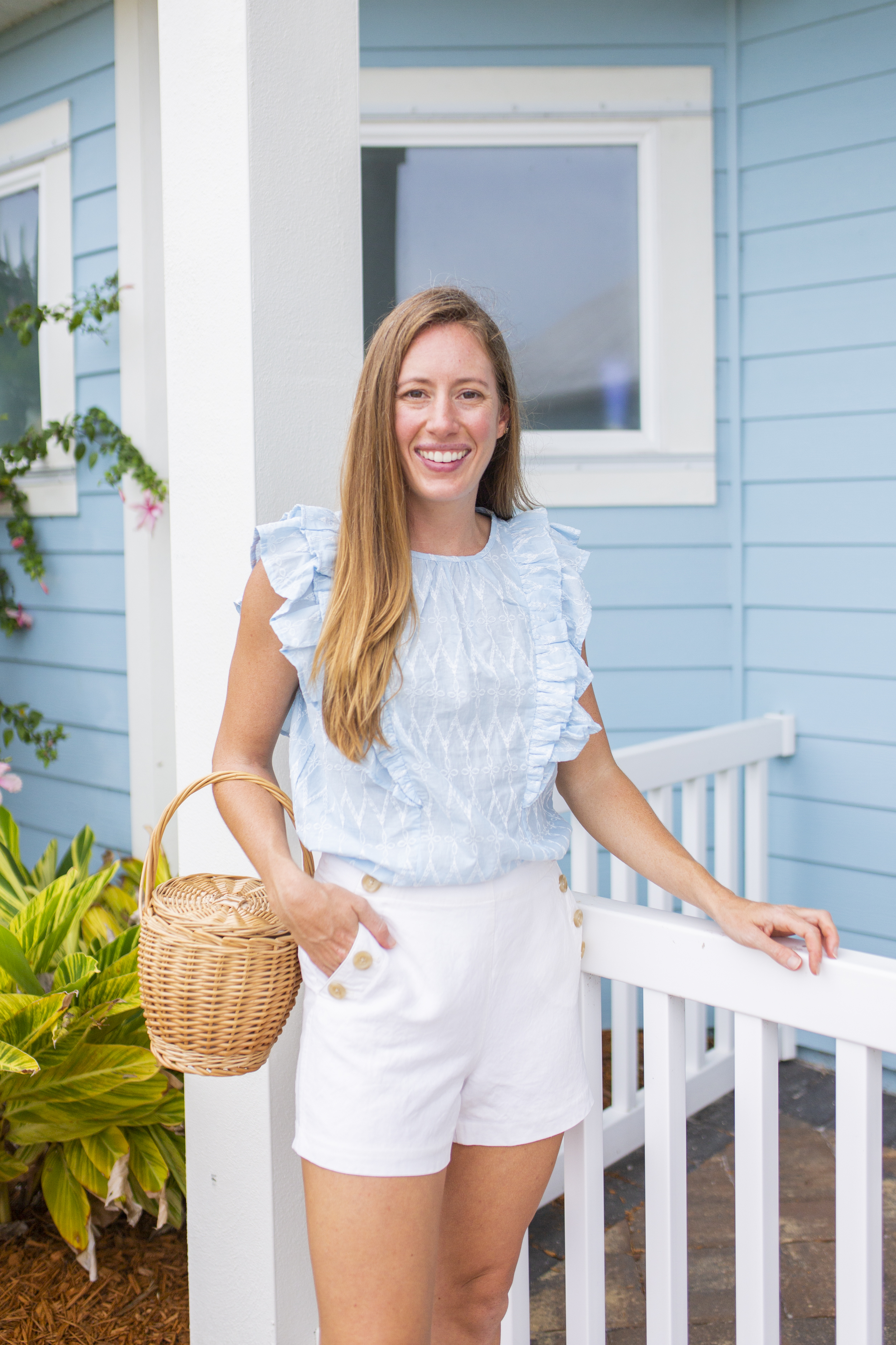 Woman smiling and wearing blue and white top styled with white shorts and a raffia bag
