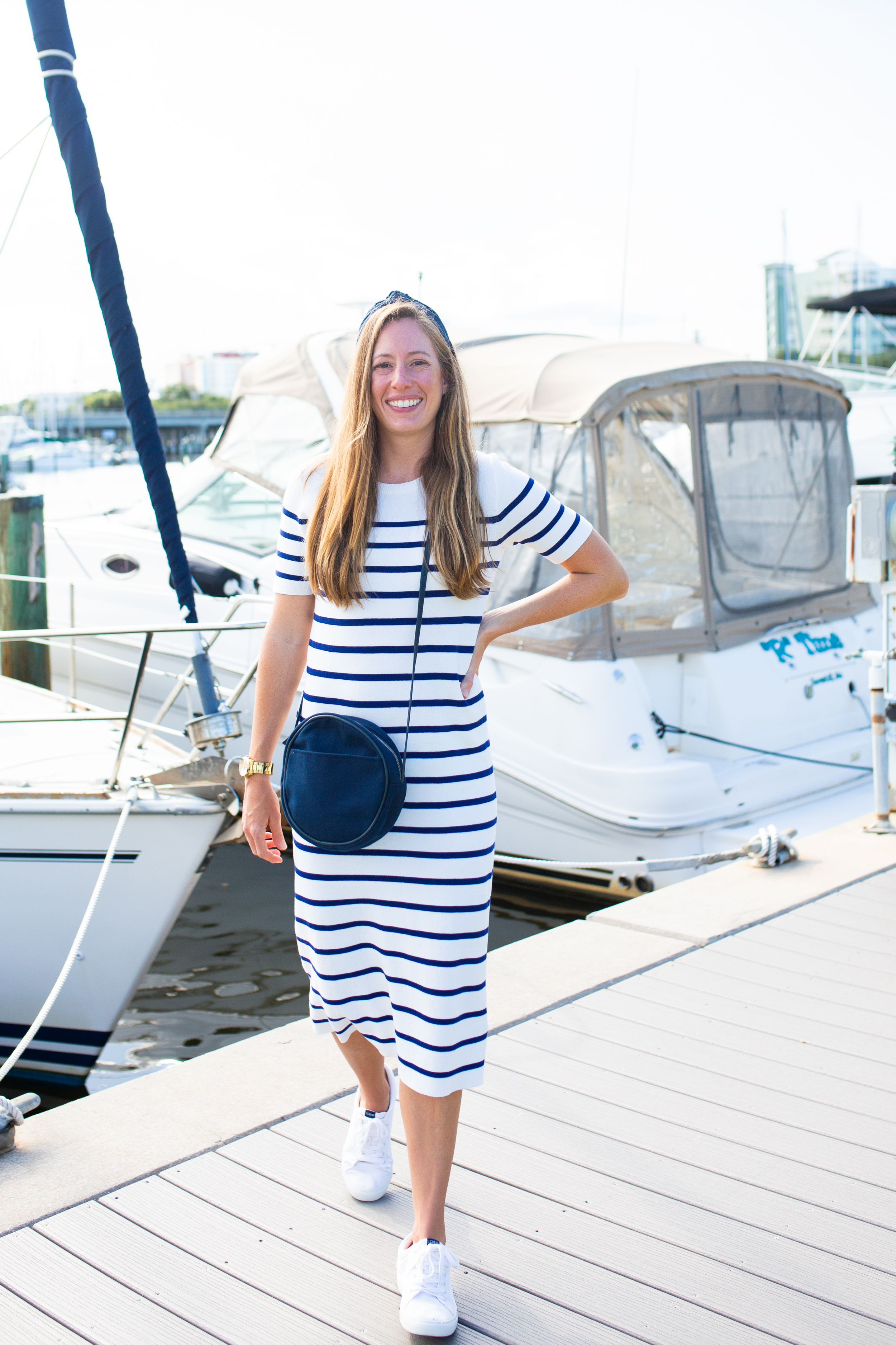 woman at the marina wearing a striped dress and denim bag
